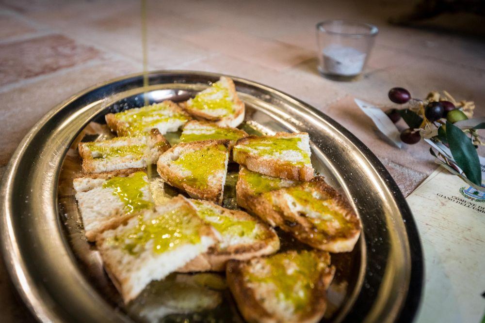 Bruschetta wird für di EVO Öl Verkostung mit gerösteten Brot vorbereitet. Photo: frantoiaperti.net